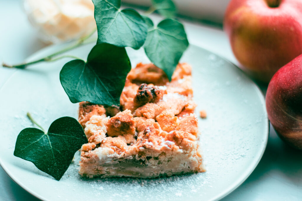 applepie with ivyleafs and blurry apples and vanillasauce behind